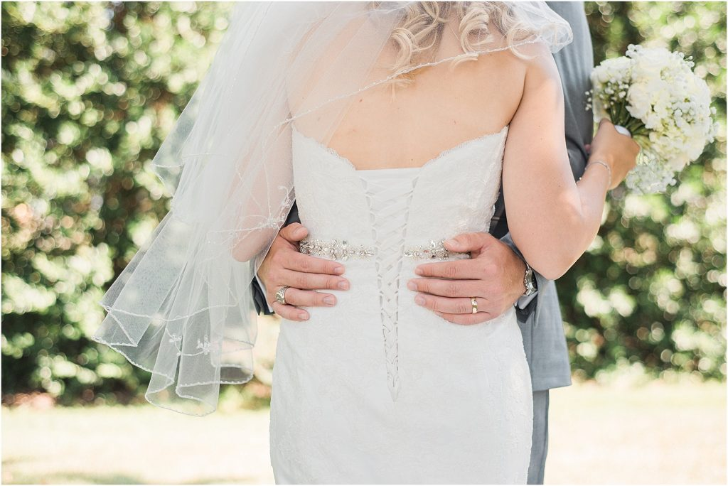 cropped detail shot of groom's hands around bride's waist lake murray chapin columbia sc fine art film wedding photography