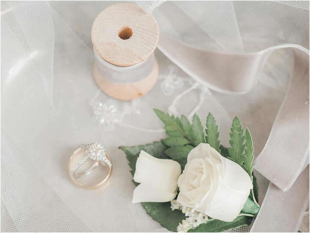 wedding details rings with ribbon veil and flowers on a silver tray at lake murray sc wedding