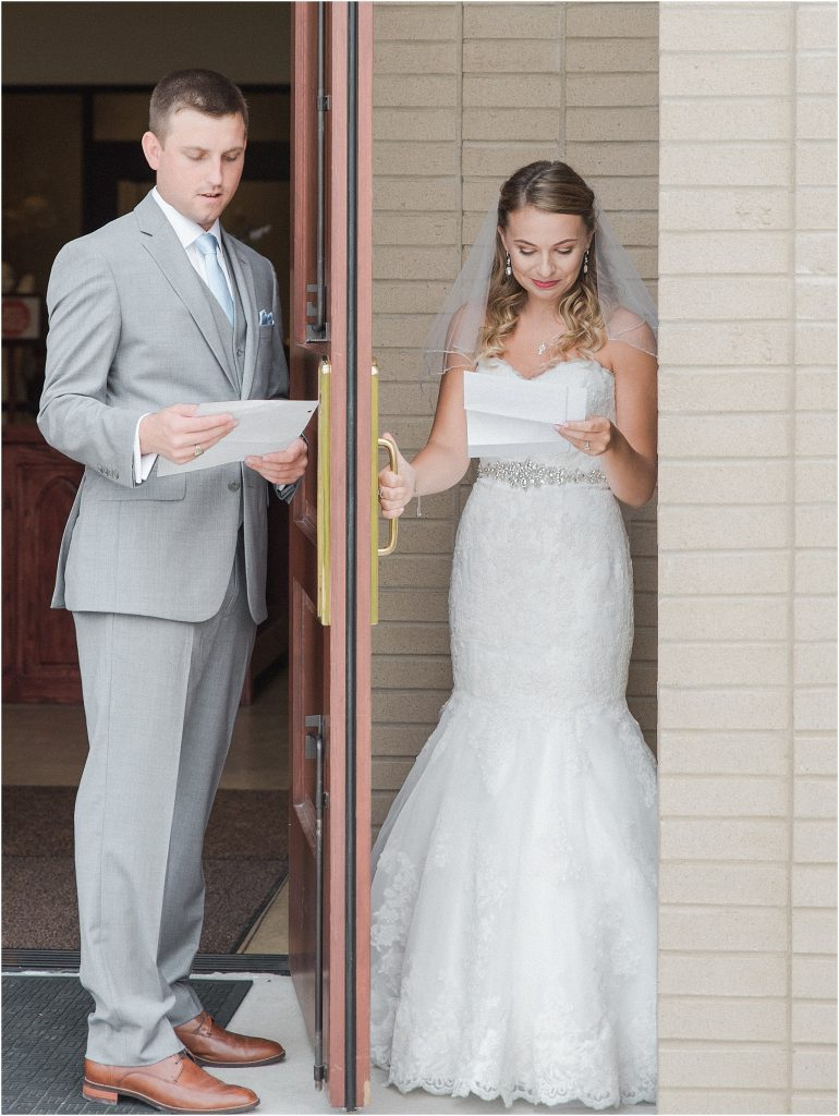 bride and groom hiding on either side of church door reading letters to each other