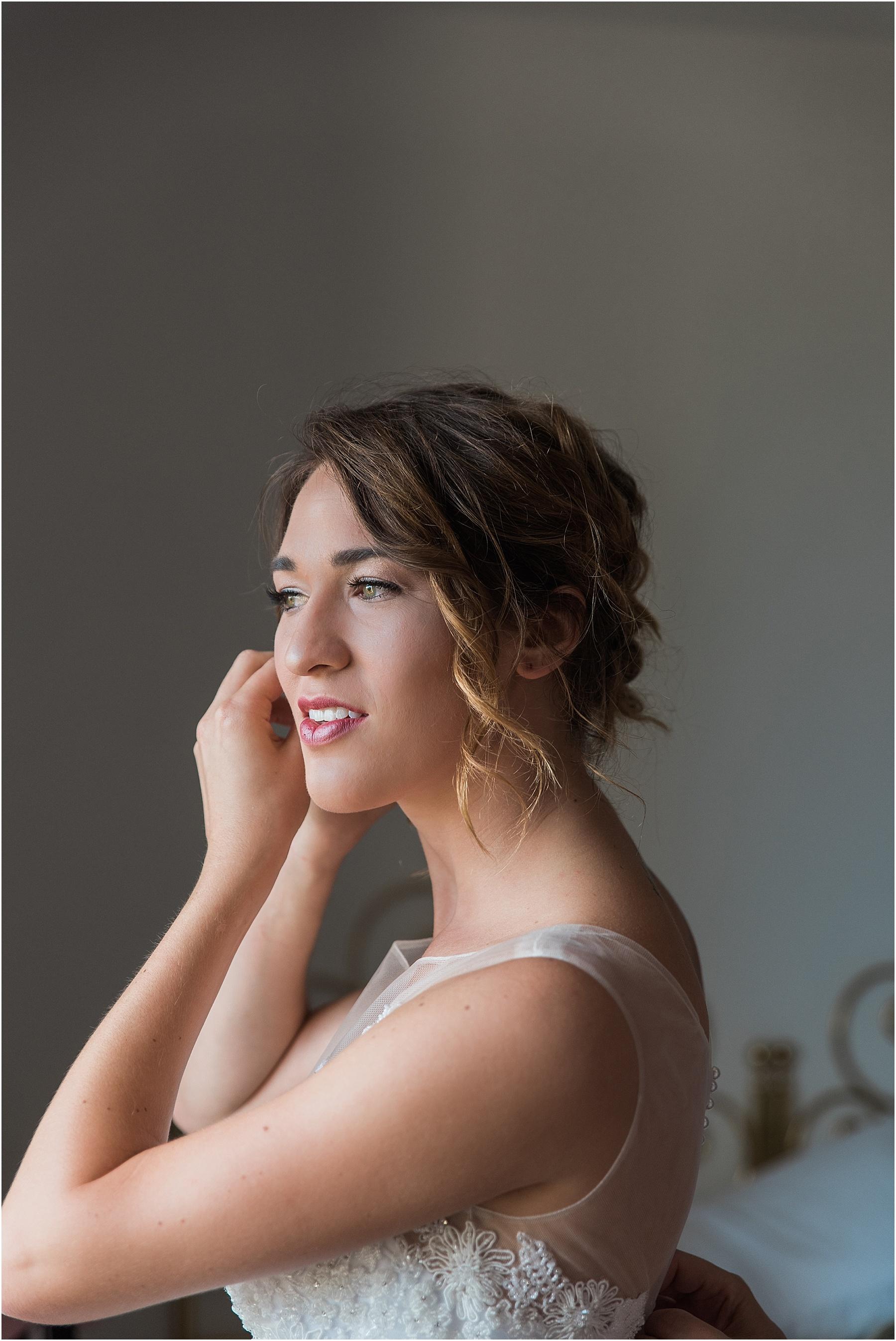 cortona italy tuscan arrezzo bride putting on her earrings and smiling beautiful window light