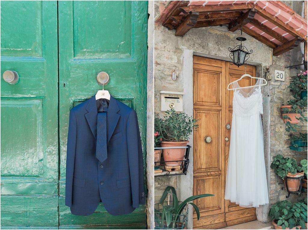 navy groom jacket on green door in cortona italy bride dress hanging on medieval door apartment in cortona italy destination wedding