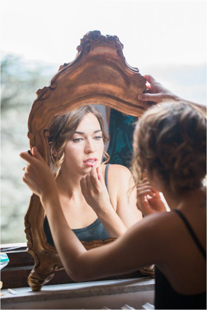 bride getting ready holding antique mirror in the window cortona italy tuscany wedding