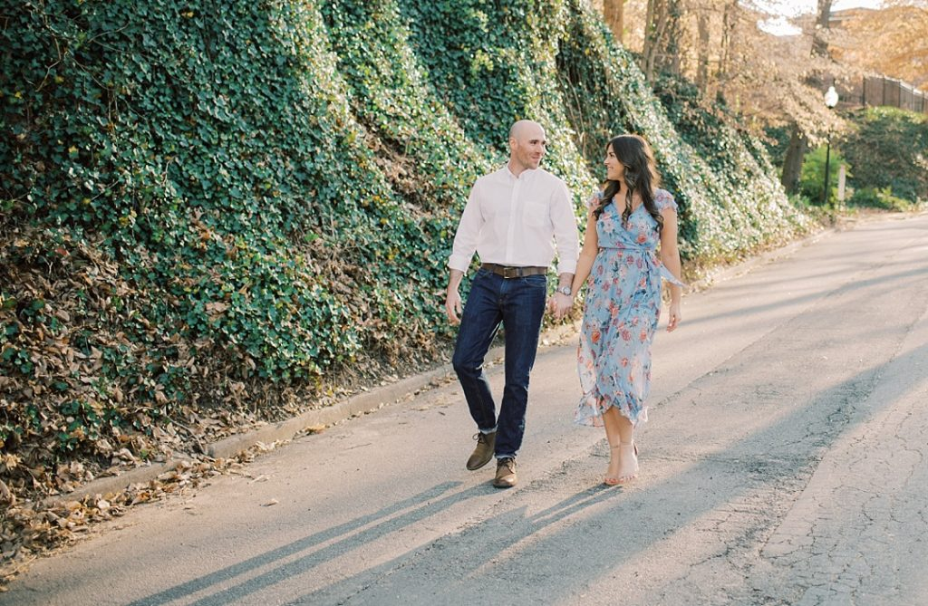 scgsah south carolina governor's school for the arts and humanities falls park on the reedy greenville sc engagement session fiance fiancee bride and groom walking beside ivy covered hill